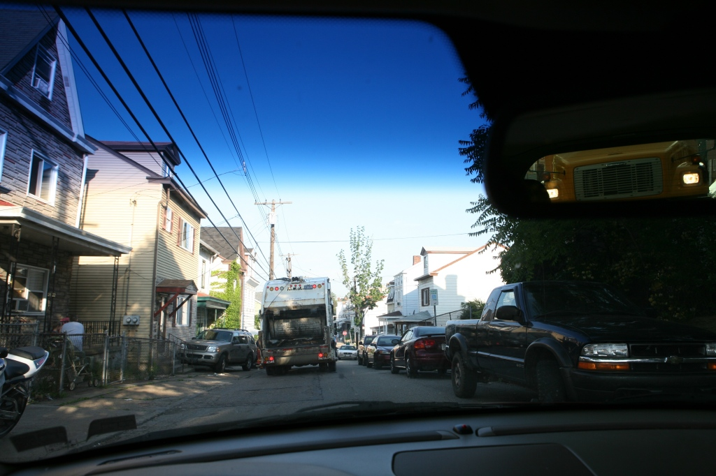You're stuck on Spring Street behind a garbage truck. It's a narrow street.