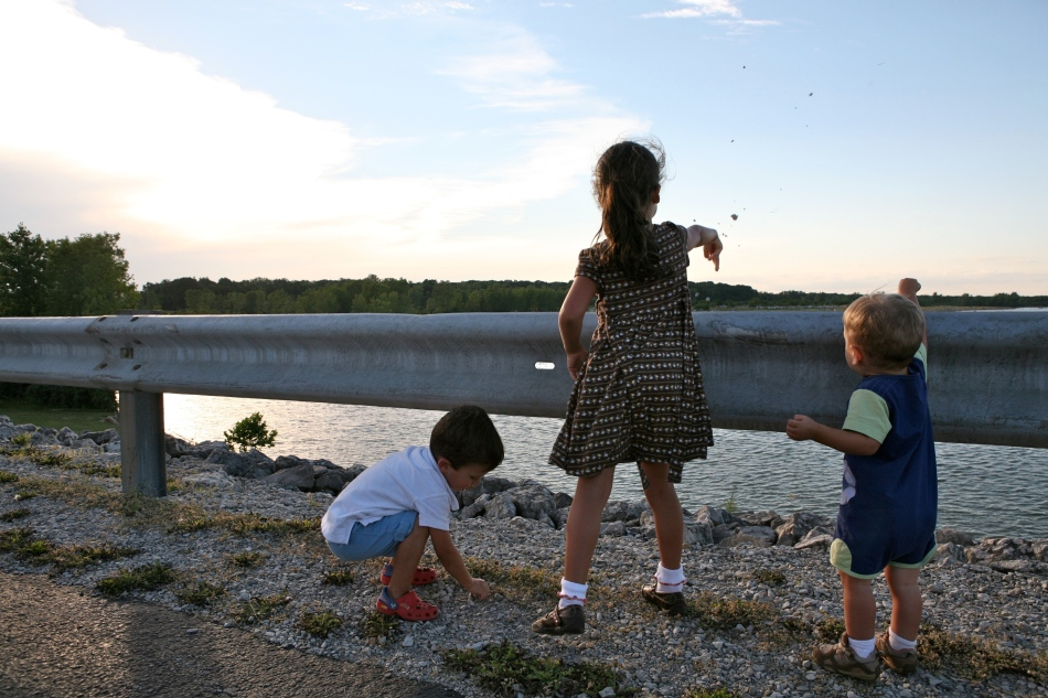 Three kids throwing small stones into the Ohio lake at dusk