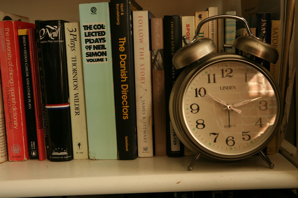 bookshelf and alarm clock