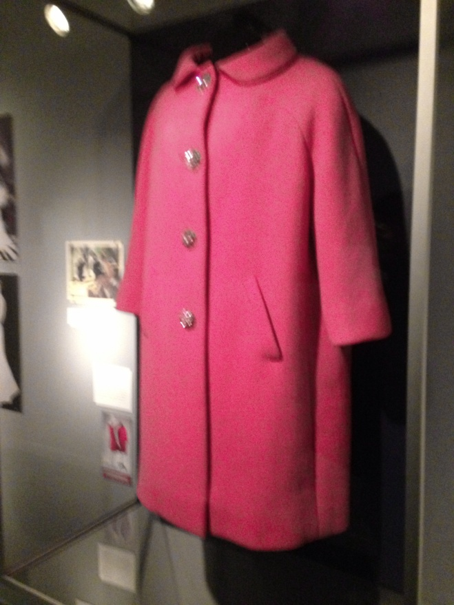 """""""A vivid pink wool coat by Norman Norell, worn by Bacall in the 1964 film Sex and the Single Girl, is on display."""""""