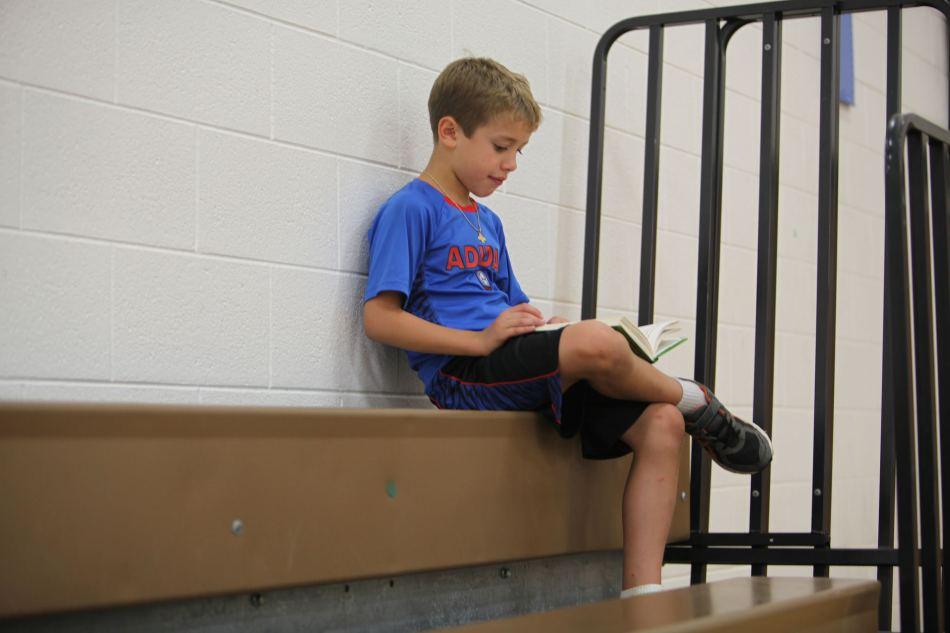jack reading a book on bleachers